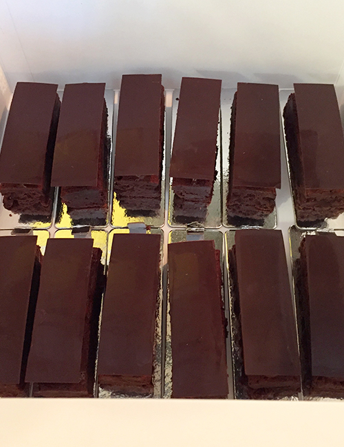 a dozen triple chocolate brownies in a catering box, viewed from above