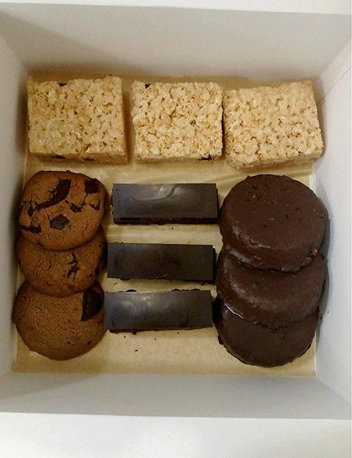 assorted box of treats includes rice krispy treats, chocolate chunk cookie, brownies, and coconut frangipane