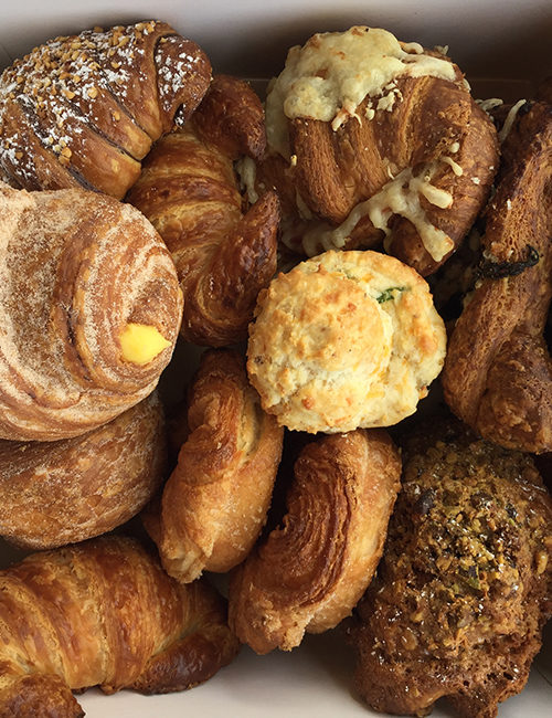 overhead view of assorted breakfast pastries in a small catering box