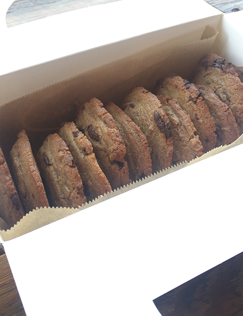a dozen chocolate chip cookies in a catering box