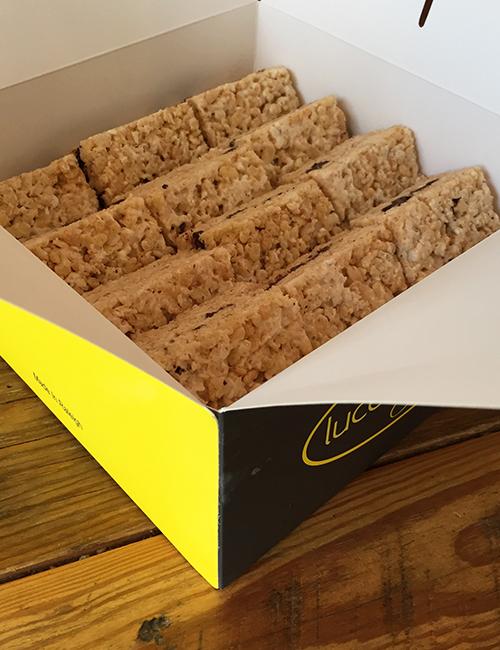 a dozen rice krispy treats in a catering to-go box