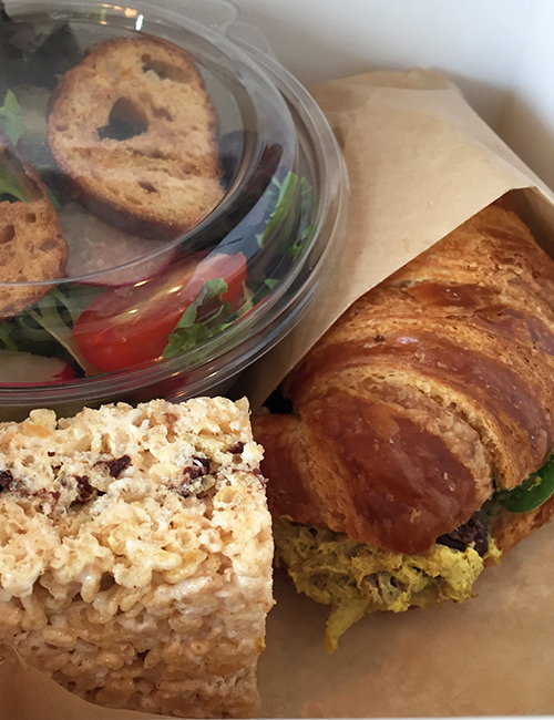 overhead view of the boxed lunch featuring the chicken salad sandwich on croissant bun