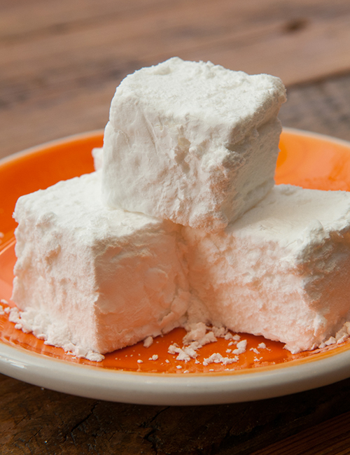 closeup of cubed home made marshmallows on a plate topped with powdered sugar