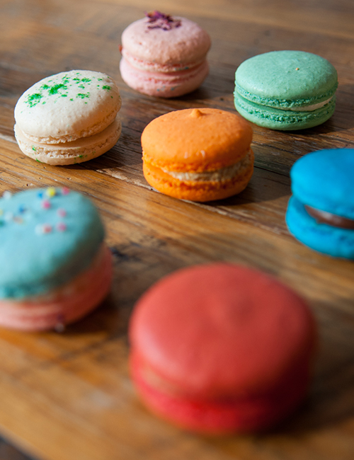 blurry photo of colorful macarons on the butcher block countertop